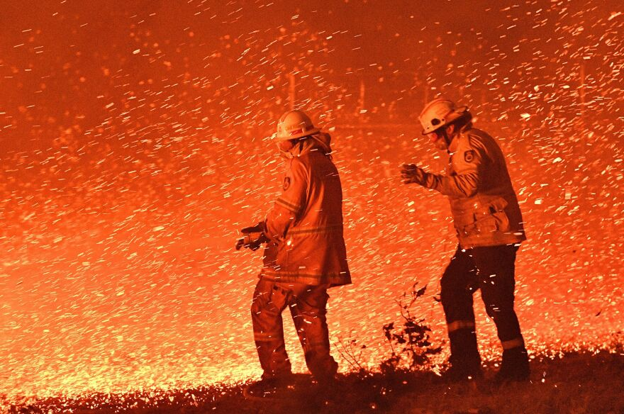 Firefighters struggle Tuesday against the strong wind in an effort to secure nearby houses from bush fires near the town of Nowra in the Australian state of New South Wales.