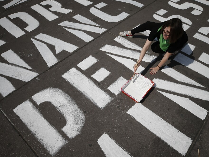 A woman helps paint the names of some of more than 3,000 victims of femicide on the plaza of the Zocalo in Mexico City, on International Women's Day, Sunday. Protests against gender violence in Mexico have intensified in recent years amid an increase in killings of women and girls.
