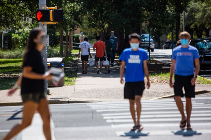 People wear face masks on the UT Austin campus in October.