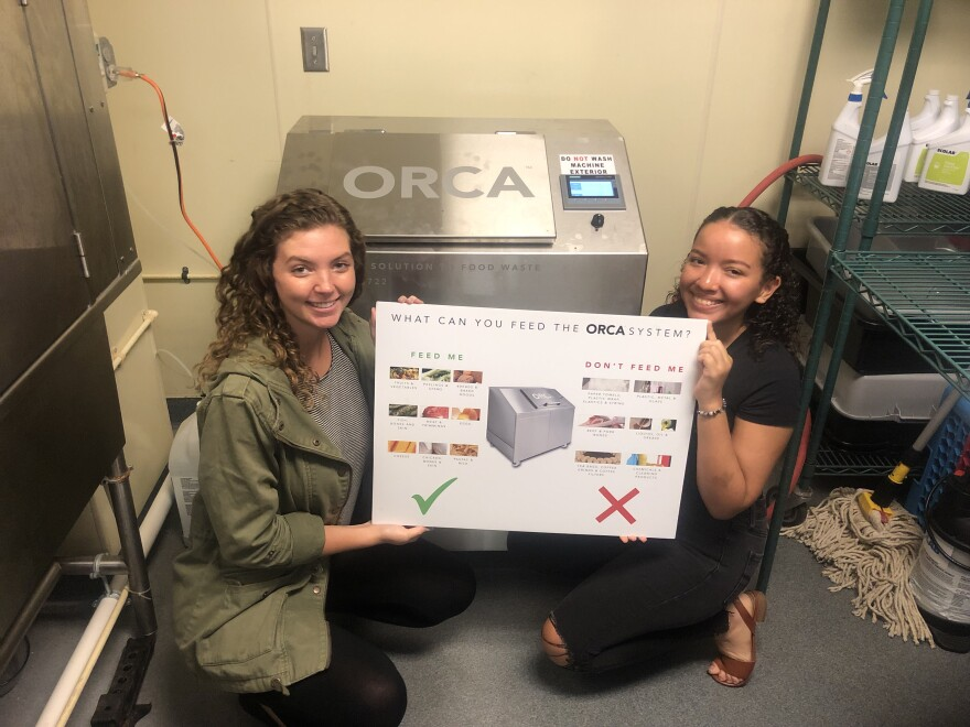 Emma Jacobs (left) and Andrea Rodriguez Campos (right) pose with a sign displaying the types of waste that can be treated by the ORCA system.