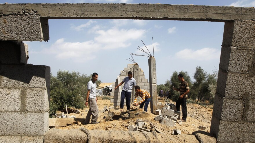 Palestinians inspect a damaged building after an Israeli airstrike in Khan Yunis in the southern Gaza Strip on Sunday.