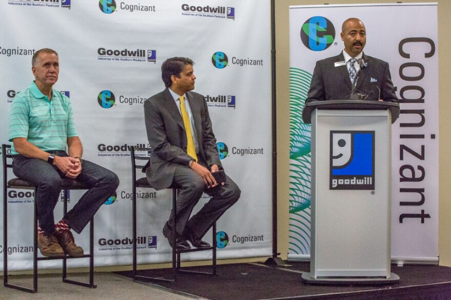 CEO Chris Jackson of Goodwill Industries of the Southern Piedmont (right) speaks Tuesday as Goodwill received a $1.5 million grant from the Cognizant U.S. Foundation. Listening are (from left) U.S. Sen. Thom Tillis and Cognizant CEO Frank D'Souza.