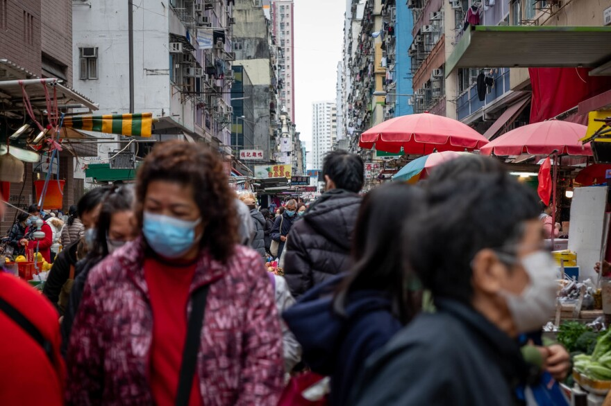 People shop in a Hong Kong market for fruits and vegetables. In this city of more than 7 million, many people have had their businesses or lives disrupted by the viral outbreak.