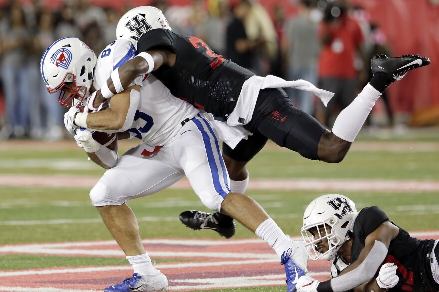 SMU tight end Kylen Granson (83) is tackled by Houston safety Gervarrius Owens, top, and safety Amaud Willis-Dalton, right, during the first half of an NCAA college football game Thursday, Oct. 24, 2019, in Houston.