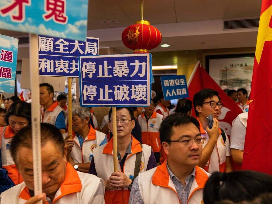 Pro-Beijing demonstrators gather at the Hong Kong Federation of Fujian Associations to show support for the Hong Kong police on Aug. 10.