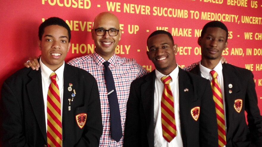 "Urban Prep founder Tim King stands in front of the school's ""We Believe"" creed with three of the school's graduates. Steven Clark (left), 17, will attend Denison University, Dwayne Mitchell, 18, will go to the University of Illinois and Derrick Little (right), 17, will attend Georgetown University."