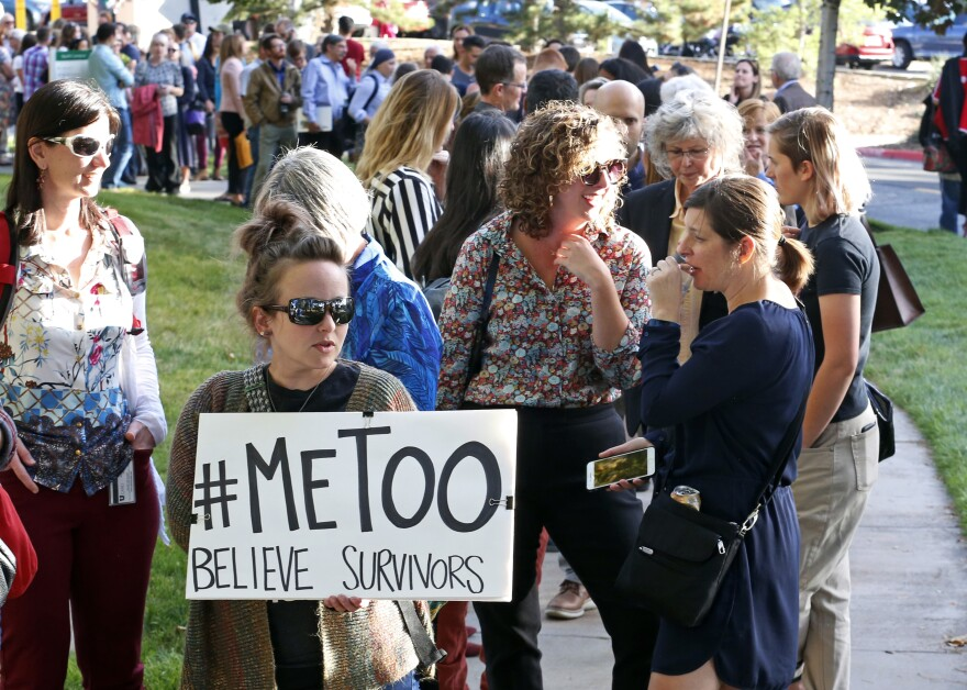 women holds up a sign that reads #metoo in front of a line of people.