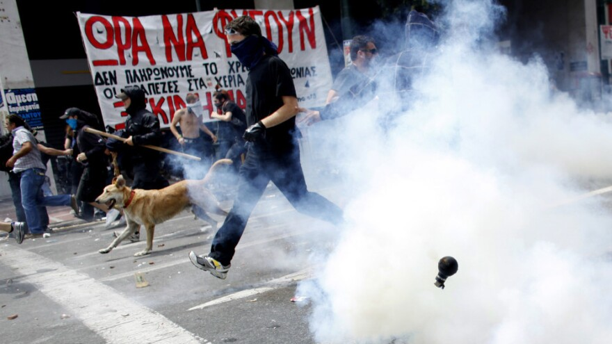 Protesters, and Loukanikos, ran from tear gas in Athens on June 15, 2011.