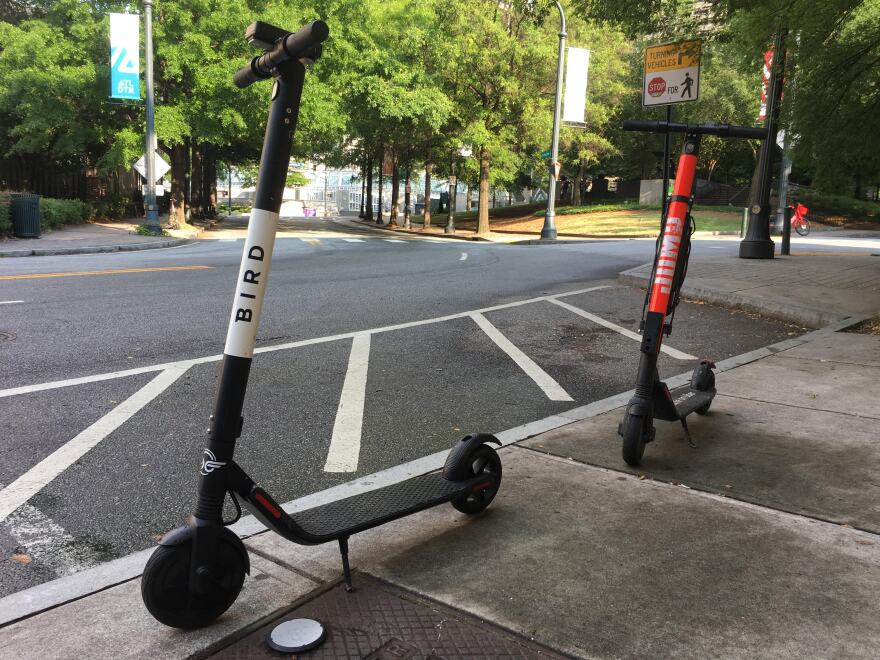 Two e-scooters are standing up on the sidewalk. A winding road with trees can be seen behind them.