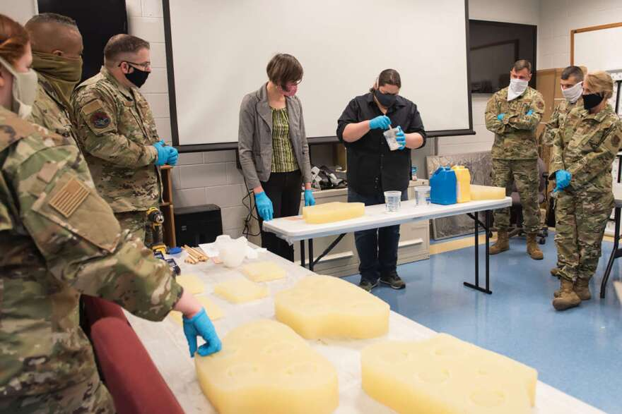 Kay Dartt, 3D fabrication manager, and Chase Molden, theater technical director, show the West Virginia National Guard how to cast an N95 respirator mask using silicone molds. The design comes from a 3D printed model developed by Dartt and Molden.