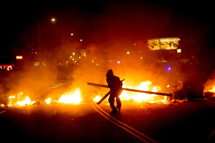 A protester adds wood to a fire burning in Oakland, Calif., on Tuesday.