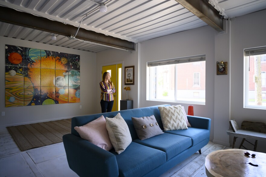 Gina Sheridan stands in the living area of her household's brand-new, shipping-container-built home.