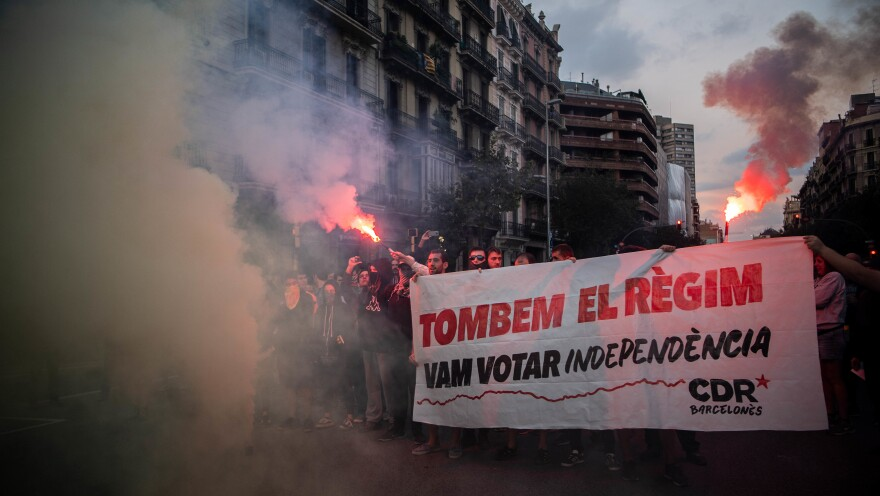 "Independence supporters block a street during a demonstration to commemorate the anniversary of the referendum last year. Their sign, written in Catalan, reads: ""Let's change the regime. We voted for independence."""