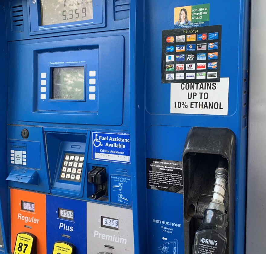 Nikki Fried's yellow and green sticker featuring her smiling face is stuck to a bright blue gas pump.
