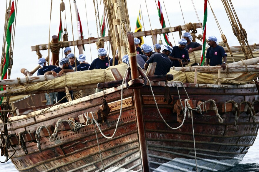 The crew of the Jewel of Muscat, a ninth century replica of an Omani trading ship, folds its mainsails as it enters into the harbor of Galle, Sri Lanka, in 2010.