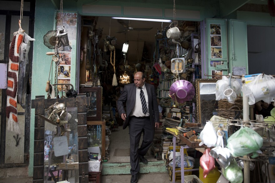 Ayman Hassouna, a Palestinian tour guide who hasn't led tourists around Gaza for 20 years, walks out of an antiques shop in the middle of the main market in Gaza's Old City.