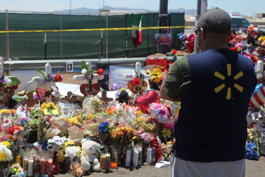 A Walmart employee from a nearby store visits a memorial outside the store where the shooting happened