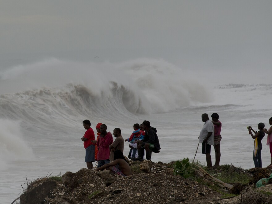 People watch waves break on the outskirts of Kingston, Jamaica, on Monday. Hurricane Matthew has generated large surf, heavy rain and wind.