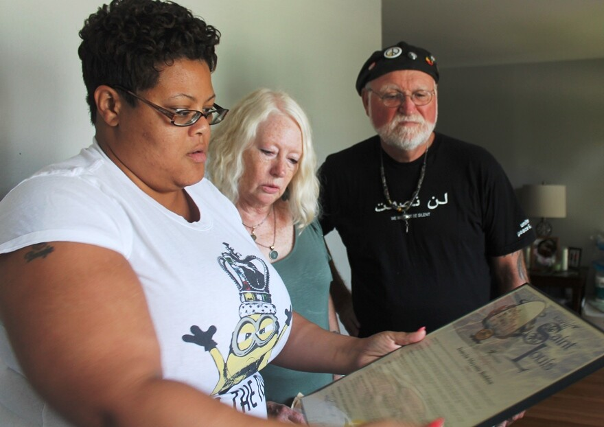 Kendric Henderson and Jane and Ivan Martin look over a proclamation Henderson received from the city of St. Louis after her daughter died.