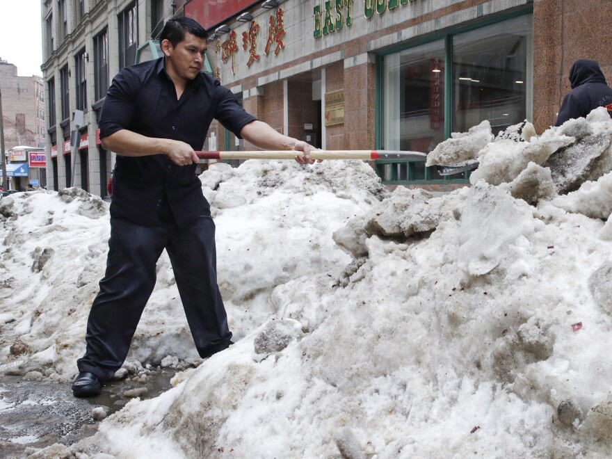 Waiter Melvin Angel shovels snow outside the restaurant he works at in Boston in April. The harsh winter in the Northeast took an even bigger toll on economic growth in the first three months of 2015 than previously estimated.