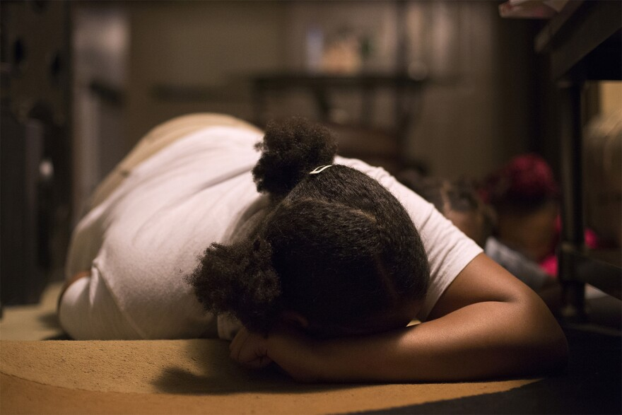 Anajah Hicks, 13, demonstrates how she lies on the floor when she hears gunshots. Anajah's mother and grandmother make sure Anajah and her siblings practice getting on the floor quickly so they can be prepared to avoid gunfire.