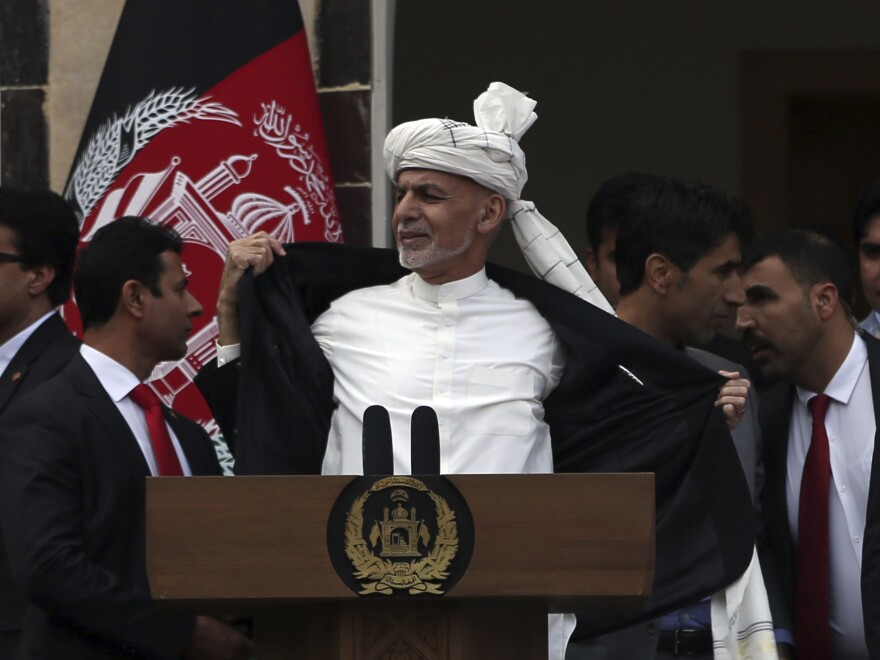 Afghan President Ashraf Ghani opens his coat after explosions were heard during his speech after he was sworn in for a second term. He told supporters he wasn't wearing a bulletproof vest.