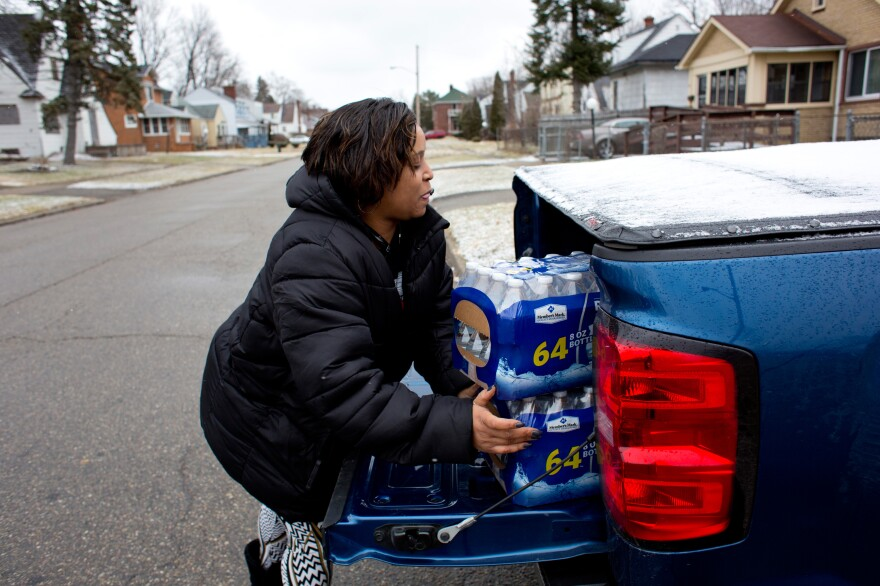 McDonald unloads cases of bottled water to take to her godbrother Brent Diggs, who is handicapped and often unable to pick up water himself, at his home in Flint.