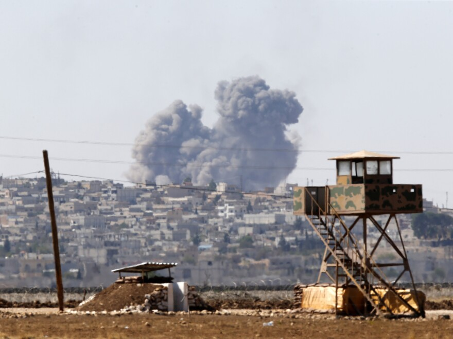 Smoke rises from the Syrian town of Kobani after an airstrike, seen from near the Mursitpinar border crossing on the Turkey-Syria border in Suruc, Sanliurfa province, on Tuesday.