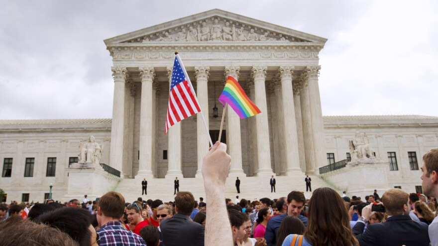 A man holds an American and a rainbow flag outside the Supreme Court in Washington, D.C., after the court legalized gay marriage nationwide.