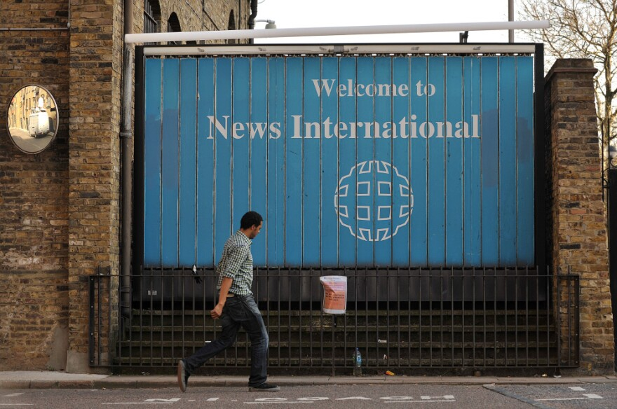 A man walks past the entrance to News International Ltd. in London on Friday. The company is apologizing to politicians and celebrities who were victims of a phone-hacking scheme at the company's tabloid <em>News of the World</em>.