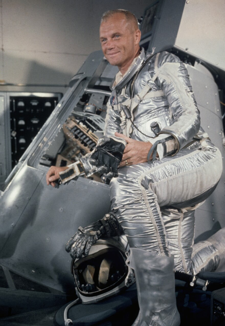 John Glenn stands beside a Mercury capsule during training at Cape Canaveral, Fla., in 1962.