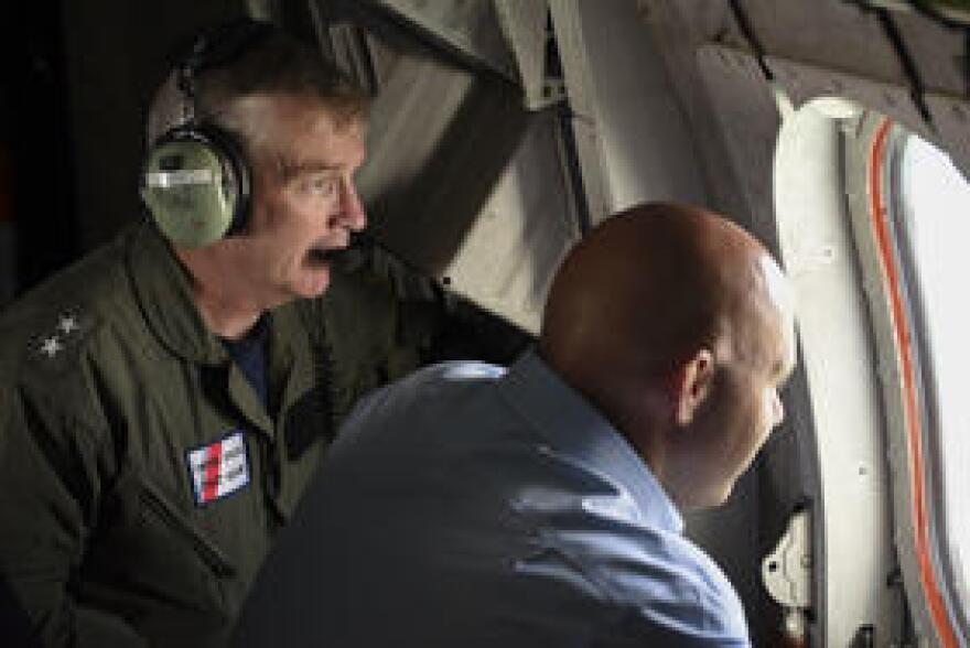 Coast Guard Adm. Peter Brown (in headphones) looking out the window of an Ocean Sentry aircraft off the coast of Florida last week.