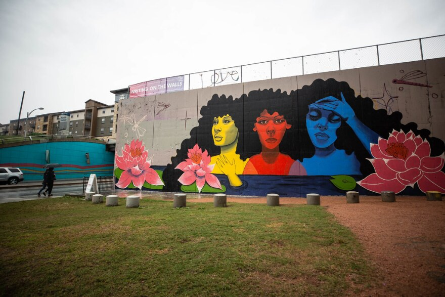 A mural of three women coming out of water with lotus flowers.