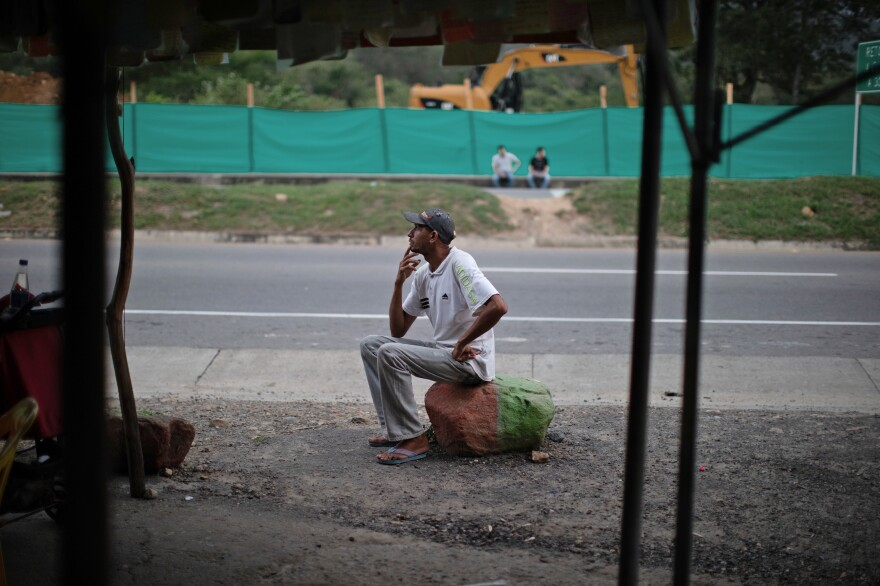 Oscar Martínez, one of more than four million Venezuelans who have left their country, rests at a roadside stand near Cucuta, Colombia.