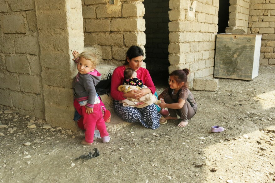 Wadha Ammo holds her youngest of five children while a girl from the village admires the baby. Ammo married her husband, Hassan Murad, while living in a displacement camp and this is the first time she has seen their new home.