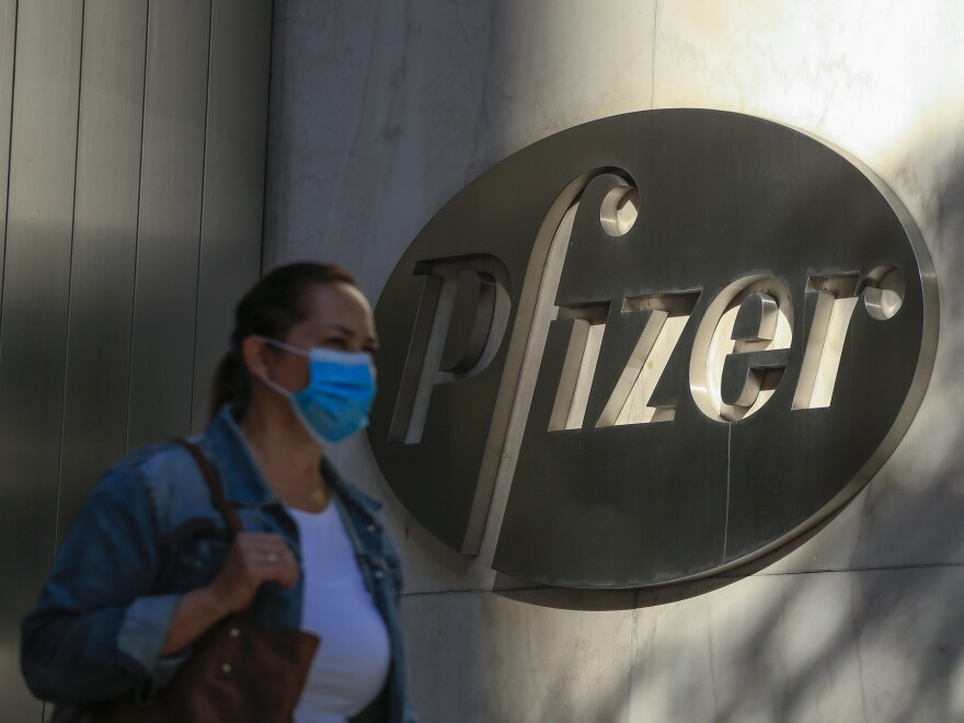 A woman wears a facemask as she walks by the Pfizer world headquarters in New York last month.