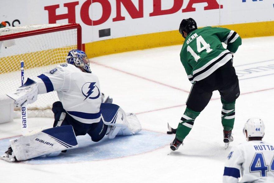 Dallas Stars' Jamie Benn shoots a puck into a goal against Tampa Bay Lightning goaltender Andrei Vasilevskiy.