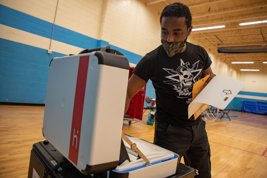 Election judge Ricky Vazquez runs his vote through the machine at the Martin Luther King Community Center in Fort Worth.