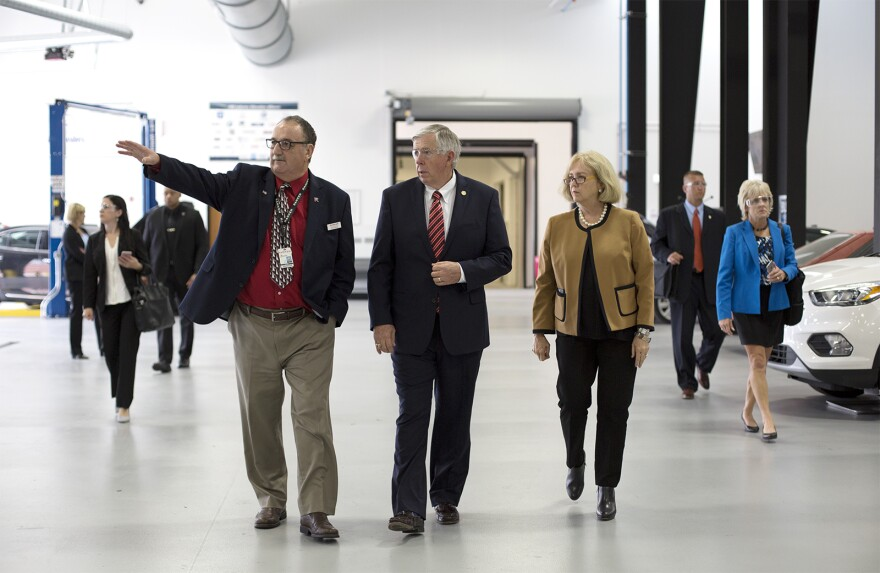 Stan Shoun, president of Ranken Technical College, guides Gov. Mike Parson and St. Louis Mayor Lyda Krewson through the school's automotive center.