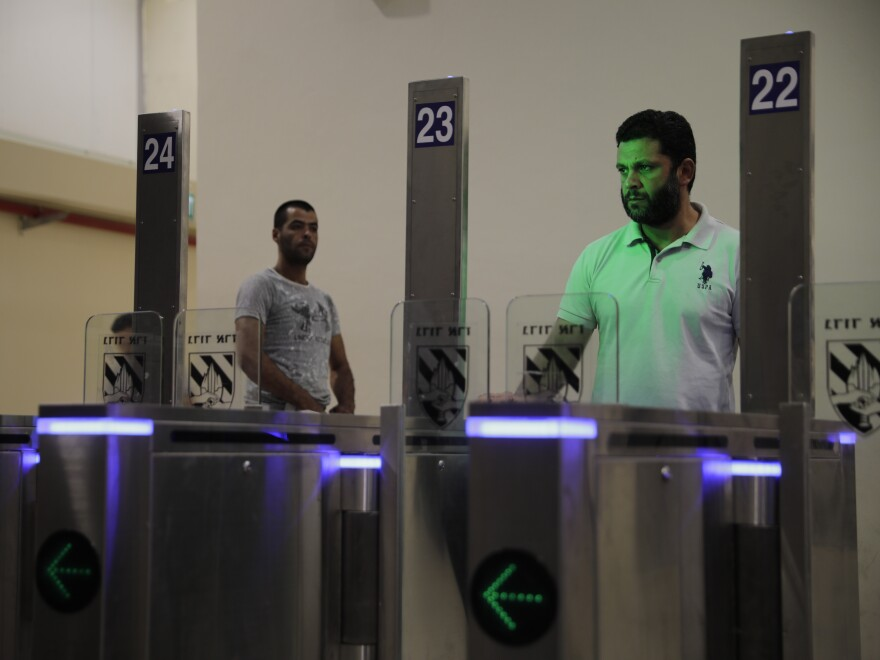 Palestinians stand in front of a biometric gate as they enter Israel at the Qalandia crossing in Jerusalem.