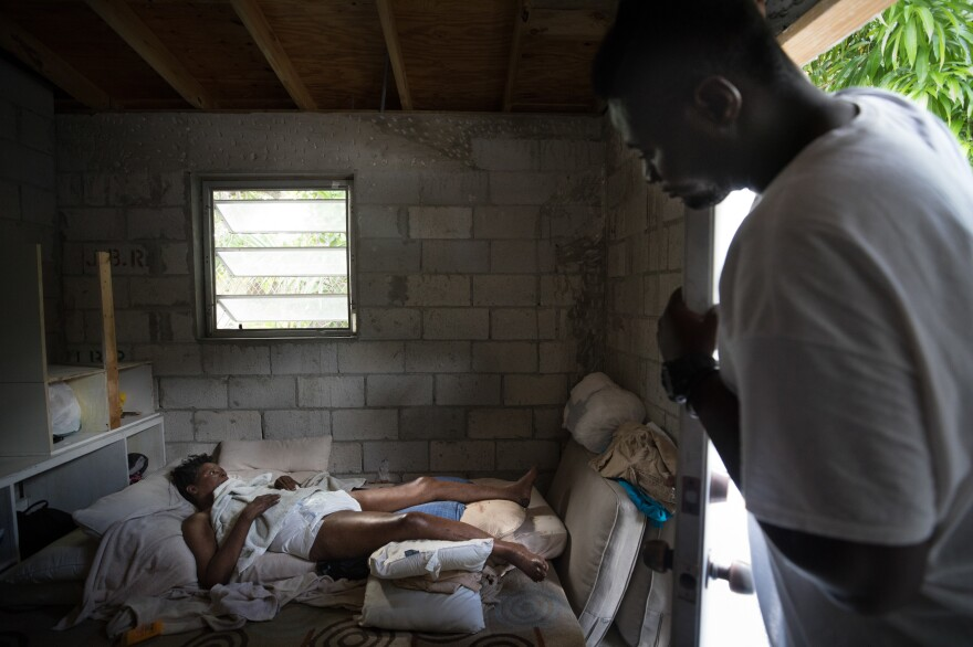 Bobson Timothee, 23, right, looks in on his mother, Lacieuse. who spends most of her time in bed.