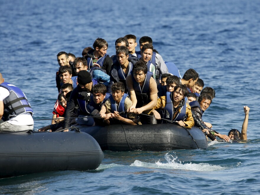 A dinghy with volunteer rescuers (left) tows a dinghy overcrowded with Afghan refugees that was drifting out of control between the Greek island of Lesbos and the Turkish coast on Saturday.