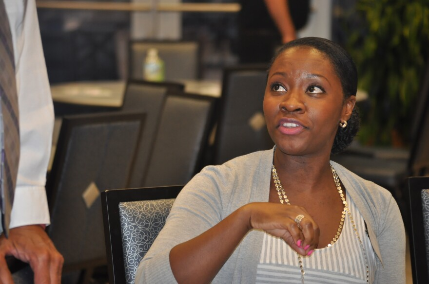Nealya Bell, who works as a nurse at a community health center, chats with Places for People executive director Joe Yancey after the presentation.