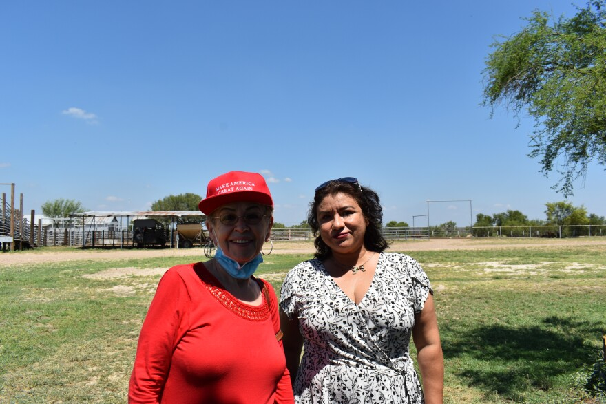 Sylvia Cervantes stands with another woman at a Latina voters event. Sylvia is dressed in a Make America Great Again hat.