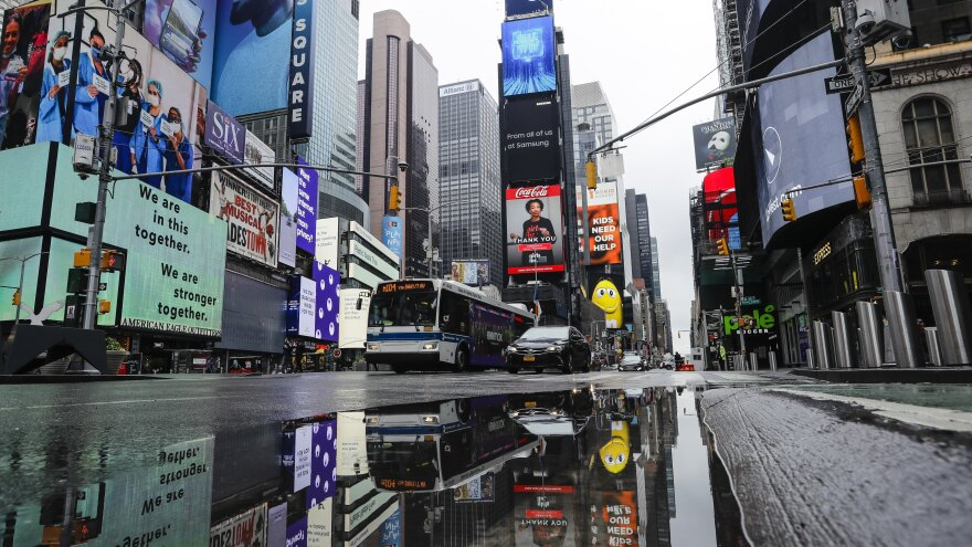 Vehicles move through a nearly empty Times Square earlier this month in New York City. On Thursday, Mayor Bill de Blasio laid out his plans for reopening the city after weeks of sweeping measures to try to contain the coronavirus outbreak.