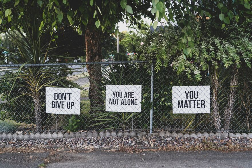 sings hung on a fence that have encouraging messages on them.
