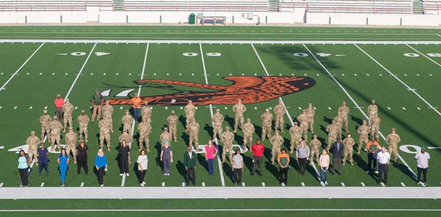 Volunteers, staff, and members of the national guard stand on a football field.