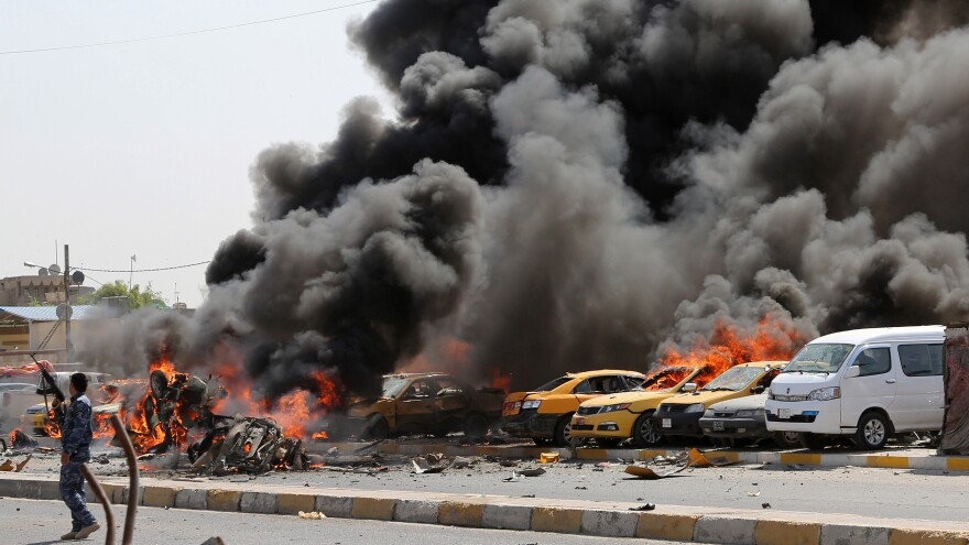An Iraqi policeman stands near burning vehicles after a bomb hit the Shiite stronghold of Sadr City in Baghdad on May 13.