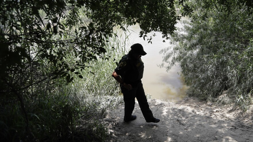 A U.S. Border Patrol agent walks along the banks of the Rio Grande near McAllen, Texas. Migrant families often cross the river illegally to enter the U.S.