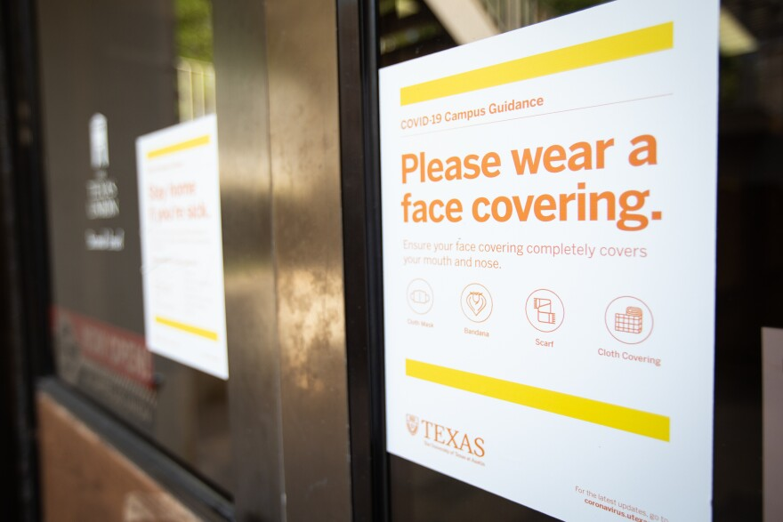 A sign on the UT Austin campus directs people to wear face coverings.